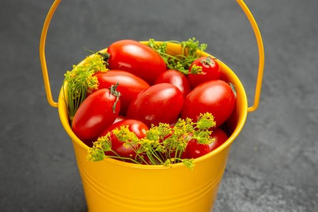 Vue rapprochée du bas seau de tomates cerises et de fleurs d'aneth sur fond sombre