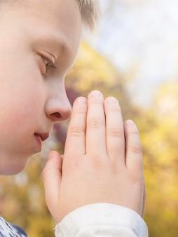 Vue rapprochée du beau petit garçon priant
