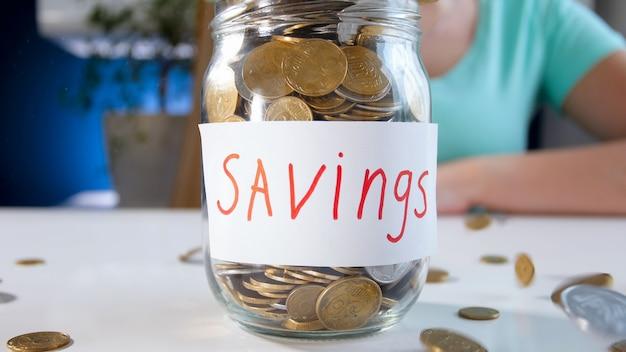 Vue rapprochée du bocal en verre pour économiser de l'argent plein de pièces sur un bureau en bois blanc. concept d'investissement financier, de croissance économique et d'épargne bancaire.