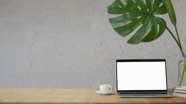 Vue rapprochée du bureau à domicile avec ordinateur portable à écran blanc, décorations et tasse de café sur un tableau blanc avec mur blanc