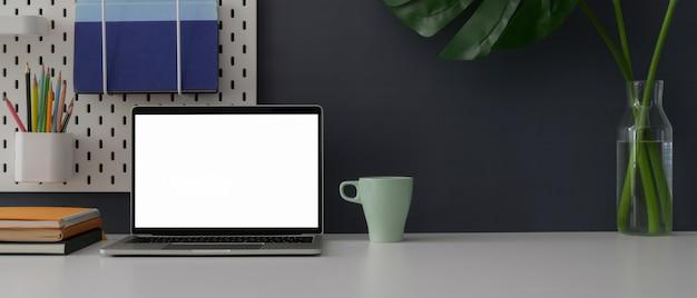 Vue rapprochée du bureau à domicile avec ordinateur portable à écran blanc, fournitures, décorations et espace de copie