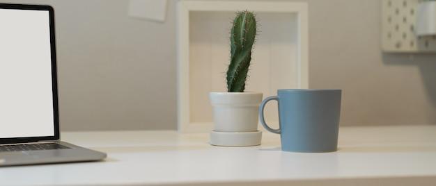 Vue rapprochée du bureau à domicile avec pot de cactus, tasse, cadre et maquette d'ordinateur portable sur un bureau blanc