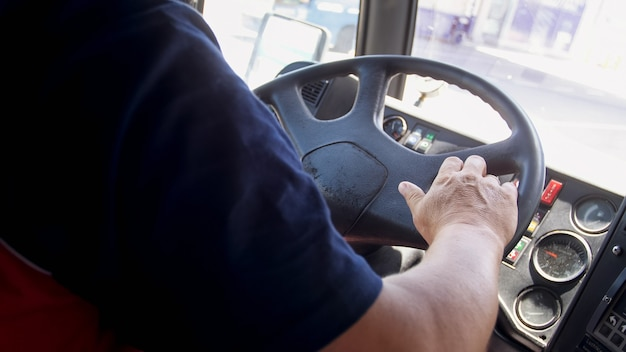 Vue rapprochée du chauffeur de bus masculin à l'aéroport conduisant la navette de bus de l'aéroport.