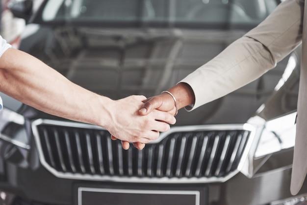 Vue rapprochée du concessionnaire et du nouveau propriétaire se serrant la main dans le salon automobile.