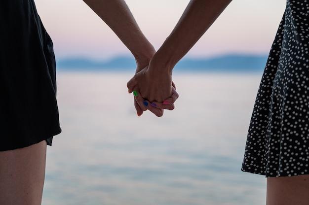 Vue rapprochée du couple gay lesbien tenant par la main debout au bord de la mer du soir.