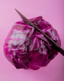 Vue rapprochée du couteau pour couper le chou violet sur fond violet