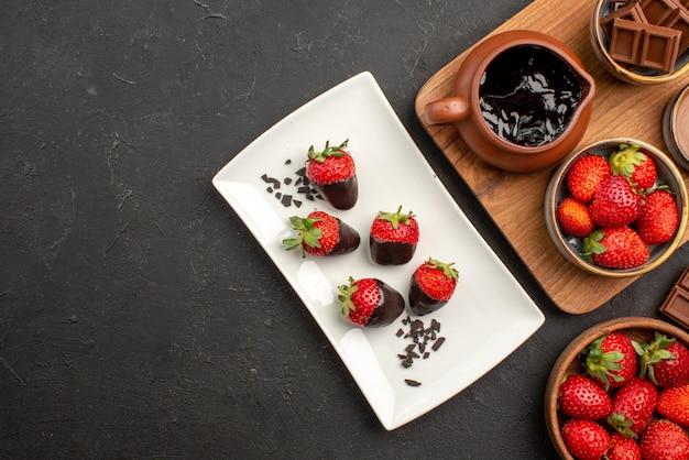 Vue rapprochée du dessus du chocolat à bord des barres de chocolat à côté de la planche à découper avec de la crème au chocolat et des fraises et des fraises enrobées de chocolat sur une assiette