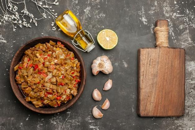 Vue rapprochée du haut de l'assiette de haricots verts bouteille d'huile d'ail citron à côté de l'assiette de haricots verts et de tomates et de la planche à découper en bois sur le tableau noir