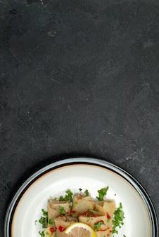 Vue rapprochée du haut de l'assiette d'un plat appétissant plat appétissant de chou farci aux herbes citron et sauce sur une assiette blanche sur une surface noire
