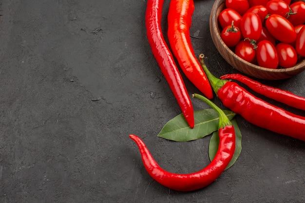 Vue rapprochée du haut demi-cercle de piments rouges et de feuilles de laurier et un bol de tomates cerises sur le côté droit de la table noire