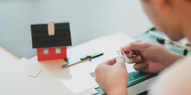 Vue rapprochée du jeune architecte masculin faisant le modèle de petite maison