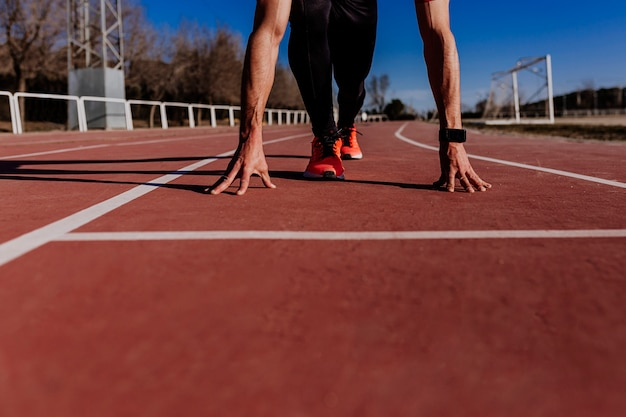 Vue rapprochée du jeune athlète musclé est au début de la ligne des pistes de course au stade. concept sportif