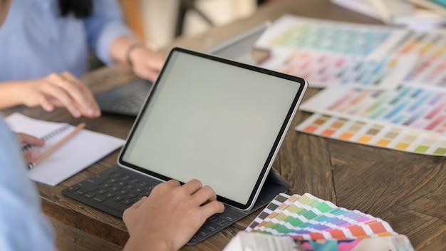 Vue rapprochée du jeune designer masculin tapant sur tablette numérique et échantillon de couleur