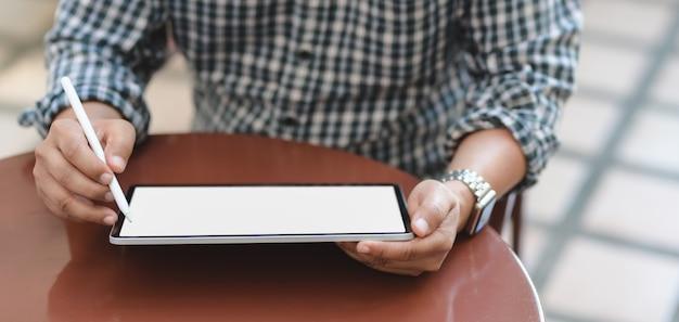 Vue rapprochée du jeune homme d'affaires travaillant sur son projet avec tablette écran blanc en position assise