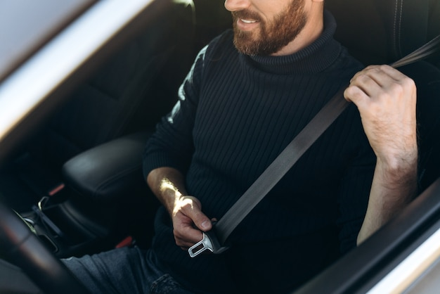 Vue rapprochée du jeune homme barbu caucasien dans une voiture attachant ses ceintures de sécurité avant la conduite. gars confiant à cheval au travail. stock photo