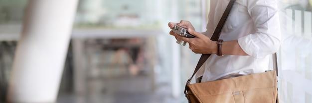 Vue rapprochée du jeune photographe masculin vérification photo sur appareil photo numérique