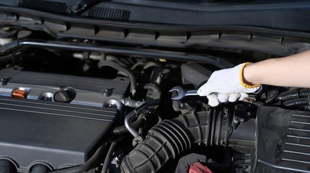 Vue rapprochée du mécanicien réparant un moteur de voiture dans un garage automobile.