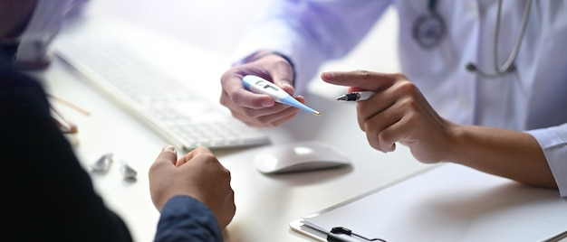 Vue rapprochée du médecin tenant un thermomètre numérique et parlant avec le patient.