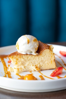 Vue rapprochée du morceau de gâteau avec boule de crème glacée décorée de tranches de fraises et de caramel
