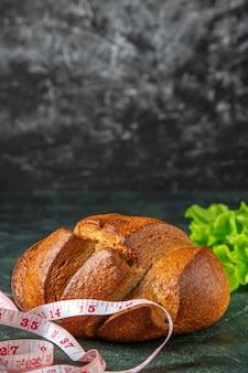 Vue rapprochée du pain noir diététique et des mètres de paquet vert sur la surface des couleurs sombres