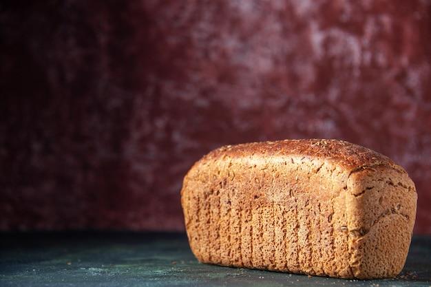 Vue rapprochée du pain noir emballé sur le côté gauche sur fond marron en détresse avec espace libre
