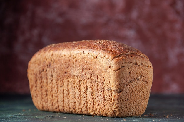Vue rapprochée du pain noir emballé sur fond marron en détresse avec espace libre