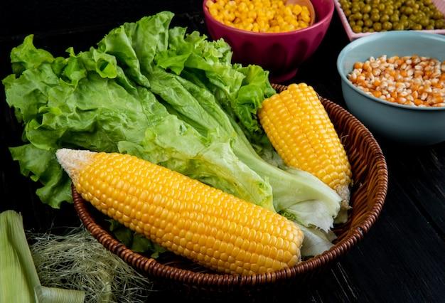 Vue rapprochée du panier avec des cors cuits et non cuits avec coquille de maïs et graines de maïs en soie