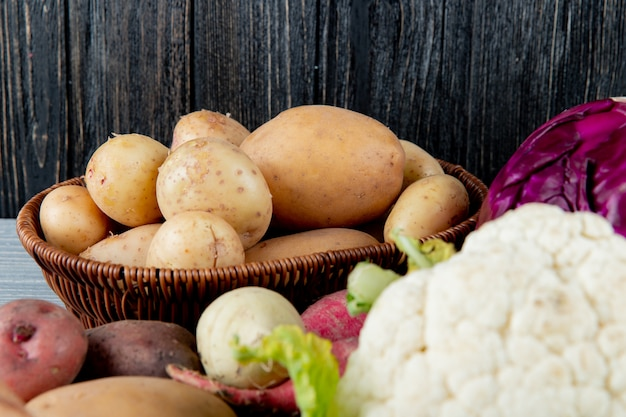 Vue rapprochée du panier plein de pommes de terre avec d'autres légumes autour sur fond de bois avec copie espace