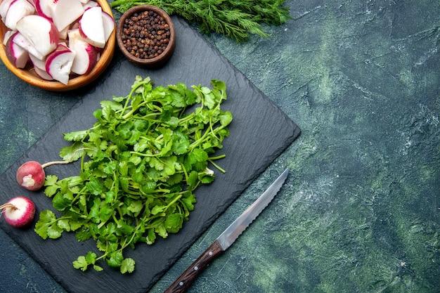 Vue rapprochée du paquet de coriandre radis frais entiers hachés poivre sur planche à découper en bois et couteau sur le côté droit sur fond de couleurs mélangées noir vert avec espace libre