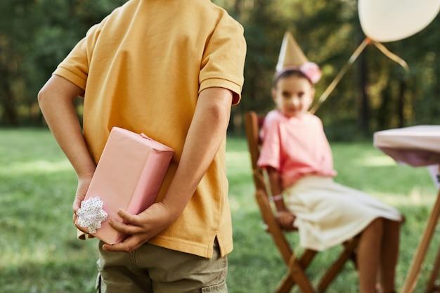 Vue rapprochée du petit garçon cachant un cadeau lors d'une fête d'anniversaire en plein air dans l'espace de copie d'été
