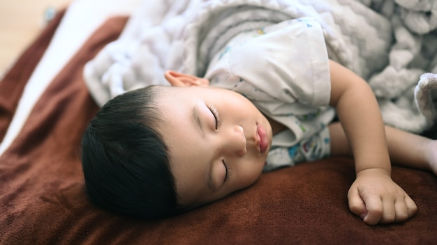 Vue rapprochée du petit garçon dormant sur le lit à la maison.