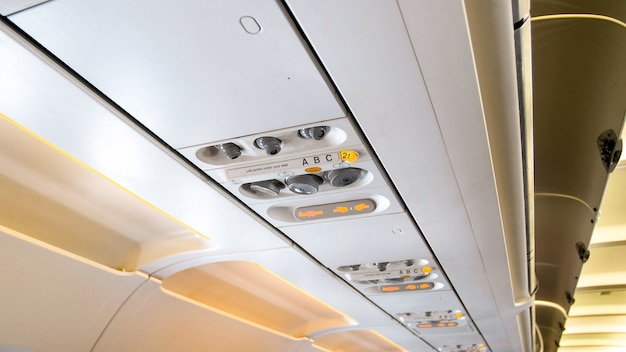 Vue rapprochée du plafond en avion avec lumières et commandes.