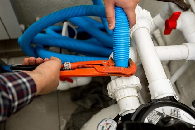 Vue rapprochée du plombier reliant deux tuyaux avec une pince rouge