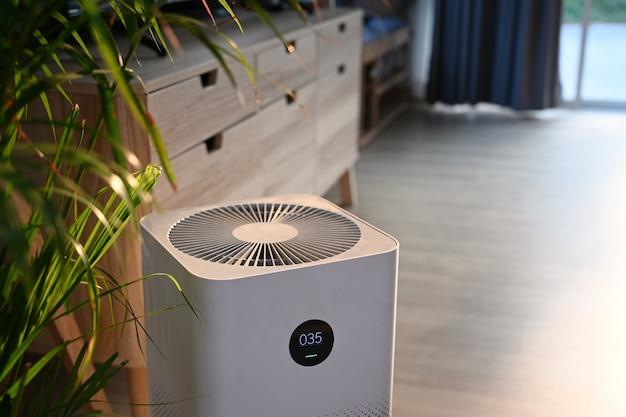 Vue rapprochée du purificateur d'air dans un salon confortable pour filtrer et nettoyer la poussière à la maison.