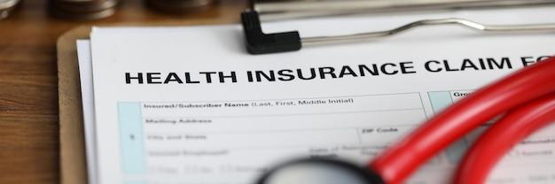 Vue rapprochée du remboursement médical avec formulaire de réclamation d'assurance maladie et stéthoscope rouge sur table. escalier de pièces.