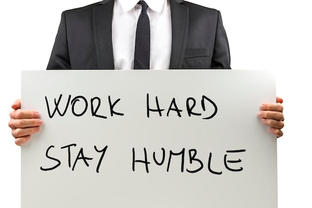 Vue rapprochée du torse isolée sur blanc d'un homme d'affaires en costume tenant une pancarte manuscrite avec un message de motivation disant - travaillez dur, restez humble.