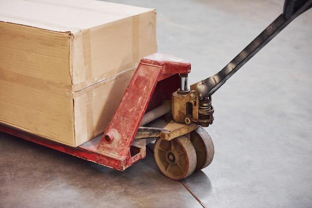 Vue rapprochée du transpalette rouge sale avec une boîte en papier dessus.