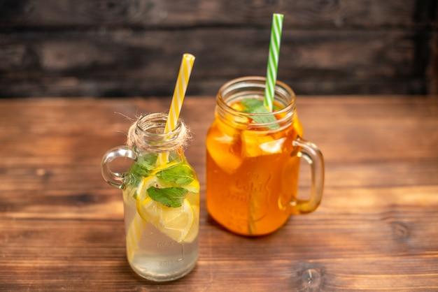 Vue rapprochée de l'eau de désintoxication fraîche et du jus de fruits servis avec des tubes sur fond marron