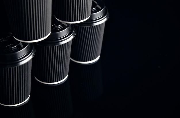 Vue rapprochée sur un ensemble non étiqueté de gobelets en carton à emporter noir fermé avec des bouchons en forme de pyramide présentés sur le côté