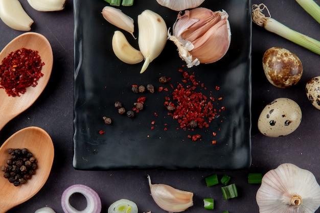 Vue rapprochée d'épices et de légumes sous forme d'oignon à l'ail sur fond marron