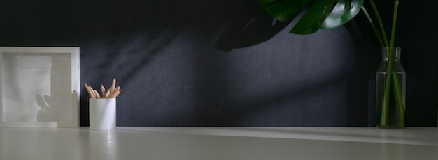 Vue rapprochée de l'espace de travail branché avec cadre de maquette, papeterie, décorations et espace de copie