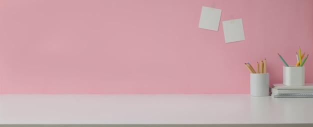 Vue rapprochée de l'espace de travail avec copie espace et papeterie sur table en marbre avec mur rose