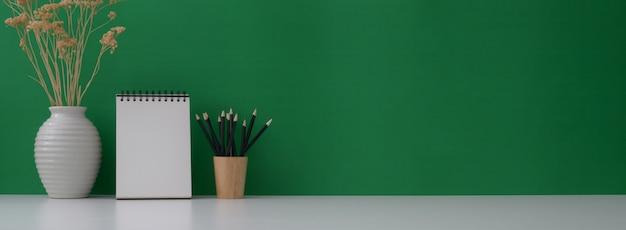 Vue rapprochée de l'espace de travail créatif avec calendrier maquette, papeterie, décoration et espace copie