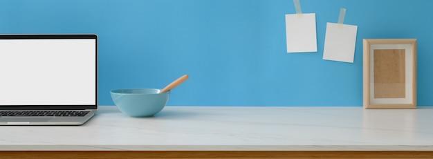 Vue rapprochée de l'espace de travail créatif avec ordinateur portable à écran blanc, petit déjeuner, cadre et espace copie sur un bureau en marbre