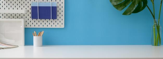 Vue rapprochée de l'espace de travail créatif avec papeterie, décorations et espace copie sur tableau blanc