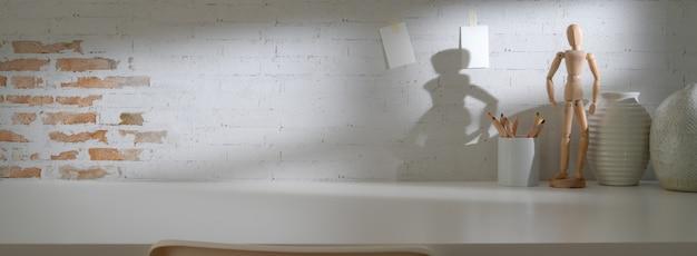Vue rapprochée de l'espace de travail moderne avec une figure en bois, des vases en céramique et un espace de copie