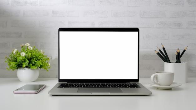 Vue rapprochée de l'espace de travail avec un ordinateur portable à écran blanc, téléphone, crayons, tasse à café et pot d'arbre sur un bureau blanc avec mur de briques
