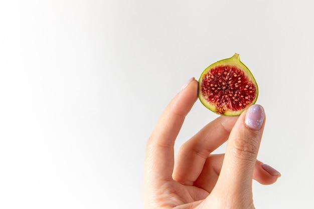Vue rapprochée de face figue douce fraîche dans les mains des femmes sur la surface blanche fruit frais doux photo