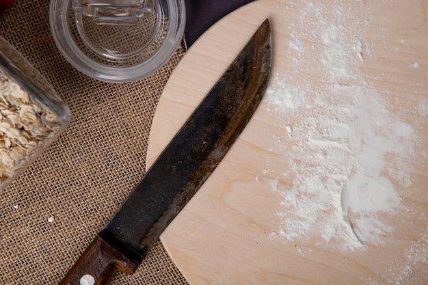 Vue rapprochée de la farine blanche avec un couteau sur une planche à découper en bois sur la surface d'un sac