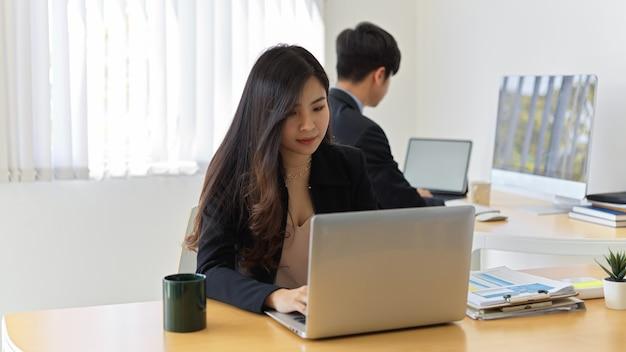 Vue rapprochée de la femme d'affaires se concentrant sur son travail avec ordinateur portable et paperasse dans la salle de bureau avec un collègue